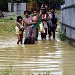 A family wades through a flooded road towards higher land in Dharmanagar after incessant rain in Tripura. (Photo: IANS)