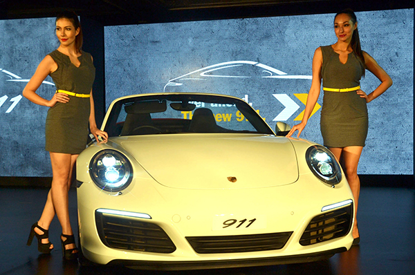 Bengaluru: Models seen with newly launched Porsche 911 in India during a press conference, in Bengaluru on July 23, 2016. (Photo: IANS)